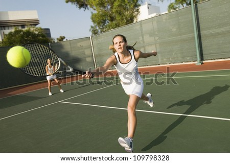 Tennis player hitting a shot with partner standing in background