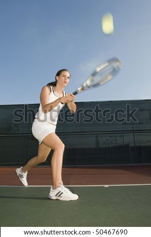 Tennis Player Hitting Backhand on tennis court - stock photo