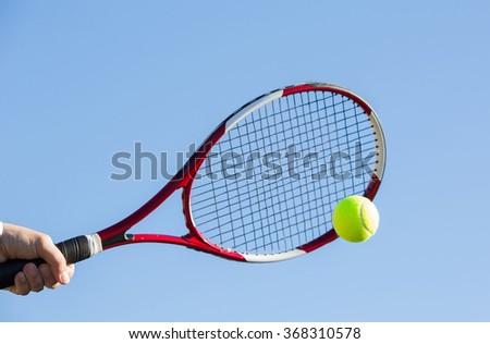Tennis player hitting the ball on a sunny day - stock photo