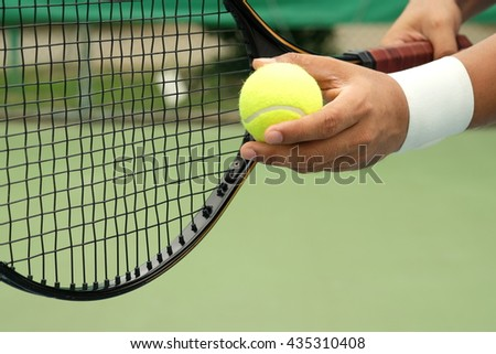 Tennis player holding racket and ball in hands
