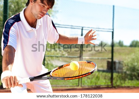 tennis player holding racket with ball - stock photo