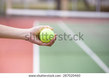 Tennis player holding the ball and getting ready to serve - stock photo