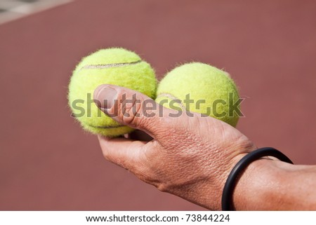 Tennis player holding two balls in his hand on court - stock photo