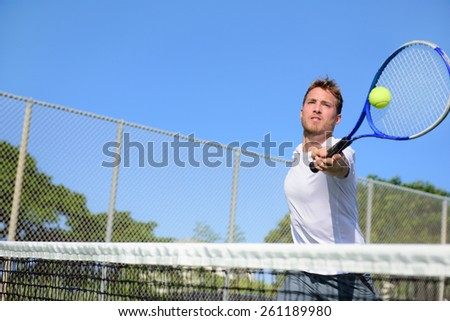Tennis player man hitting ball in a volley. Male sport fitness athlete playing tennis on outdoors hard court in summer. Healthy active lifestyle concept. - stock photo