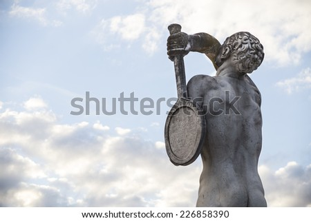 Tennis player. Marble statue and sky - stock photo