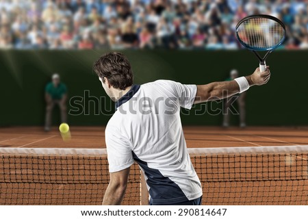 Tennis player returning a ball on a clay tennis court.