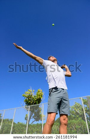 Tennis player serving playing outdoors sport. Man serve with throwing tennis ball up. Male athlete training practicing outdoors in summer. - stock photo