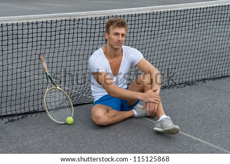 Tennis player sitting besides the net on outdoor tennis court.