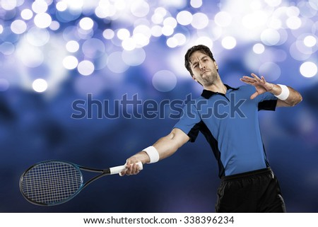 Tennis player with a blue shirt, playing on blue lights background.
