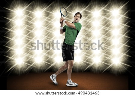 Tennis player with a green shirt, playing in front of lights.