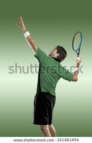 Tennis player with a green shirt, playing on green background.