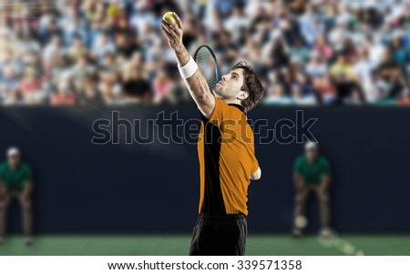 Tennis player with a orange shirt, playing on a fast tennis court. - stock photo