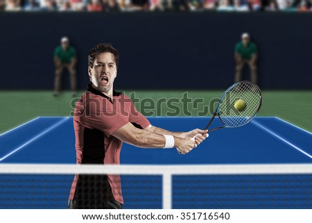 Tennis player with a pink shirt, playing on a fast tennis court.