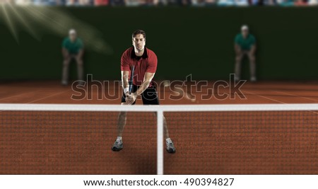 Tennis player with a red shirt, playing on a clay tennis court.
