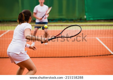 Tennis players playing a match on the court on a sunny day - stock photo