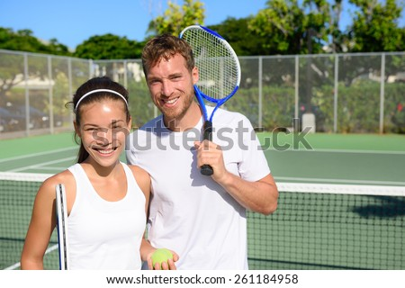 Tennis players portrait on tennis court outdoor. Couple or mixed double tennis partners after playing tennis outside in summer. Happy young people, woman and man living healthy active sport lifestyle. - stock photo