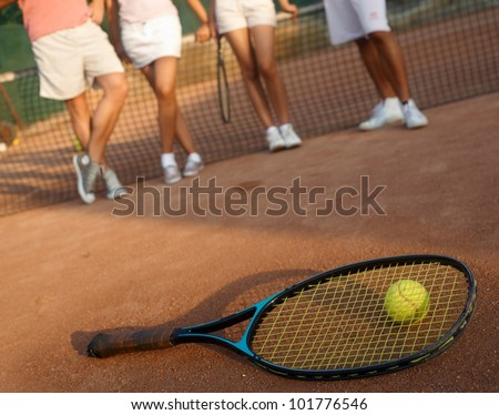 Tennis racket and ball on hard court, players standing in the background, only legs to be seen.