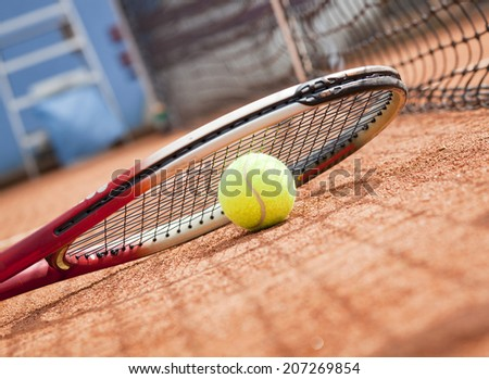 tennis racket and ball on the clay court - stock photo