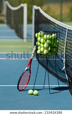 Tennis racket and balls in basket on blue hard court