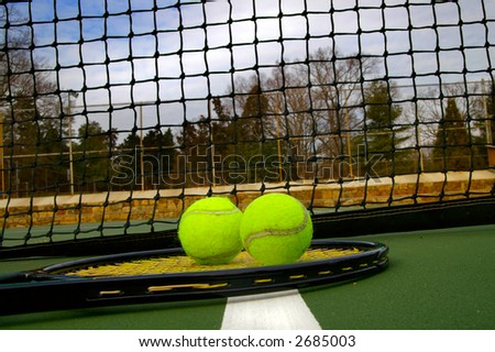 Tennis racket and balls on the court