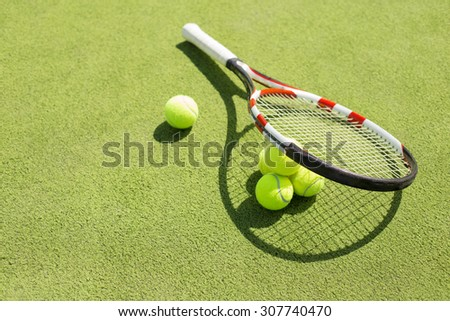 Tennis racket and balls on the court grass - stock photo