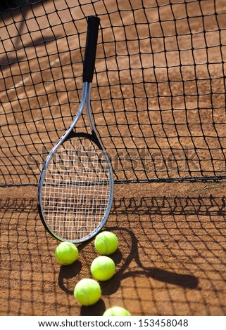Tennis racket and balls, tennis court - stock photo