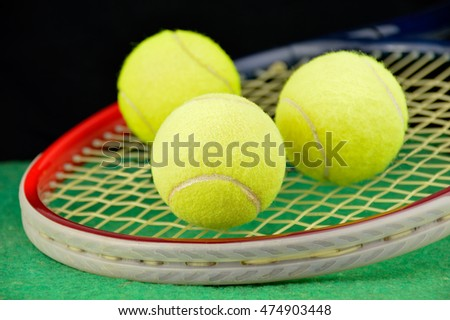 Tennis racket and three ball over the tennis court and black background