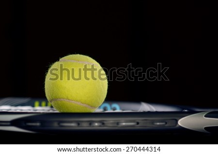Tennis racket isolated on black background with tennis ball - stock photo