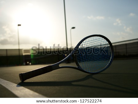 Tennis Racket on the Court backlit by the Setting Sun - stock photo