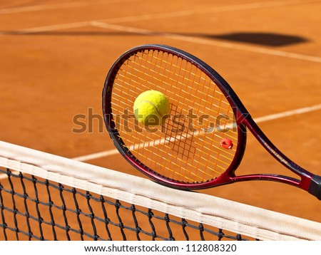 tennis racket on the net in the middle of the tennis court - stock photo