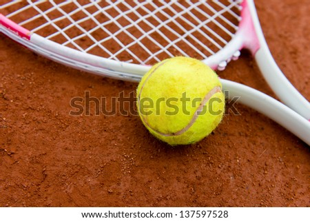 Tennis racket with ball on a clay court