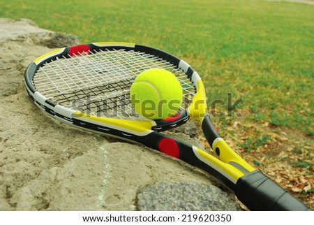 Tennis racket with ball on the court - stock photo