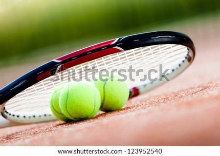 Tennis racket with balls on clay tennis court - stock photo