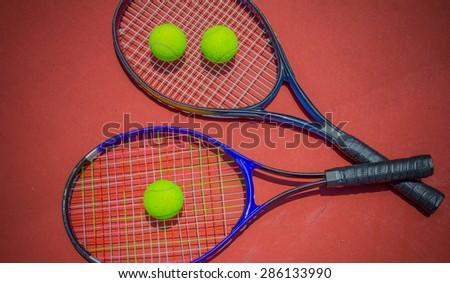 Tennis racket with balls on tennis court - stock photo
