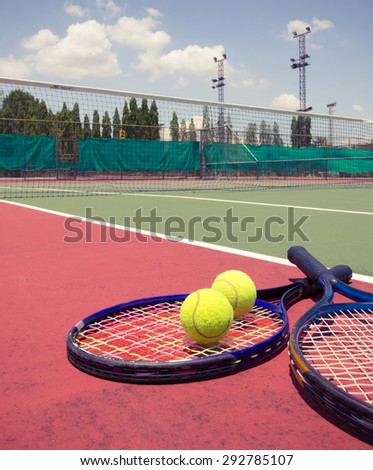 Tennis racket with balls on tennis court