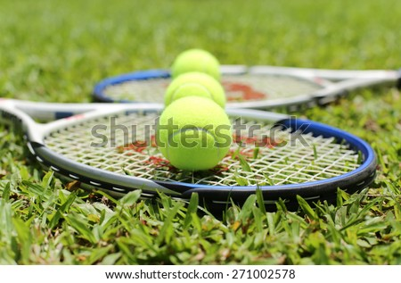 Tennis racket with balls on the grass in blur background - stock photo