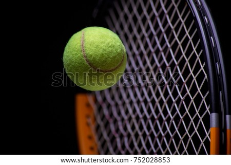 Tennis racket with tennis ball in yellow foreground
