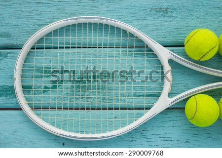 tennis racket with tennis ball on green wood texture - stock photo