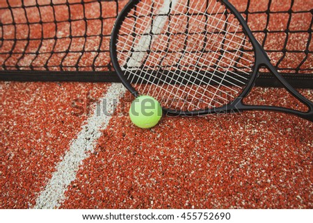 Tennis racket with yellow ball are near the net on a tennis court - stock photo