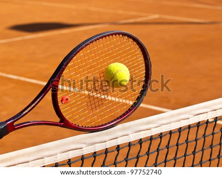 tennis racquet on the net in the middle of the tennis court - stock photo
