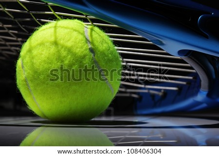 Tennis racquet resting on top of a tennis ball - stock photo