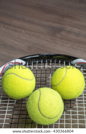 Tennis racquet with three green balls on the wooden background