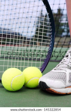 Tennis shoe, racket and balls on a hard court in front of net. - stock photo