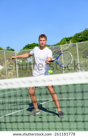 Tennis. Tennis player hitting ball in volley by the net. Male athlete playing outdoors on hard court practicing in summer. Young Caucasian man living healthy active fitness sport lifestyle outside. - stock photo