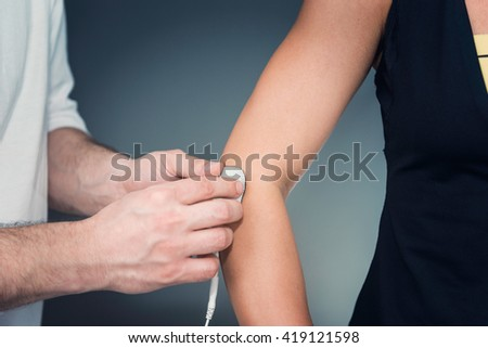 TENS treatment in physical therapy - therapist placing electrodes onto patient's elbow