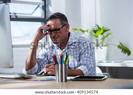 Tense man working on his graphics tablet in office - stock photo