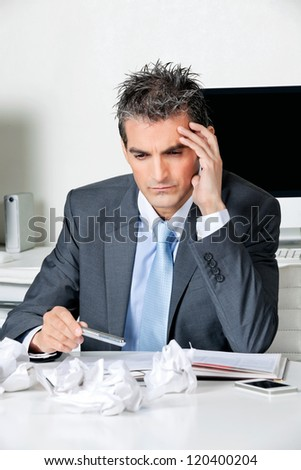 Tensed businessman sitting at desk in office - stock photo