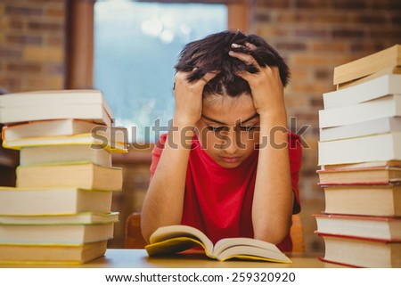 Tensed little boy sitting with stack of books at desk