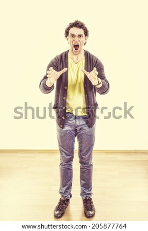 Tensed man under pressure yelling with cramped hands expressing anger, Stressed young casual man troubled with problems - stock photo