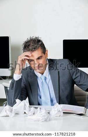 Tensed mid adult businessman sitting at desk in office - stock photo